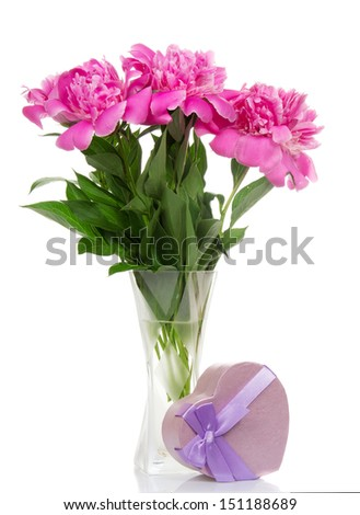 Peonies in a glass vase, and a gift box with a ribbon, isolated on white