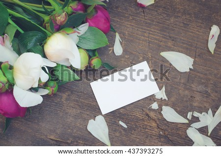 Peony background. Fuchsia, pink and white peonies on old wooden table with an empty card for text. Happy Mothers Day. Mother's Day greetings card. Valentines Day. Copy space. Toned image. - stock photo