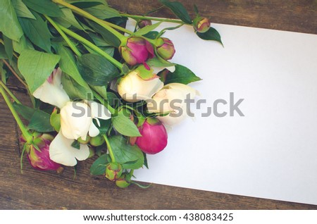 Peony background. Fuchsia, pink and white peonies on old wooden table with an empty sheet of paper for text. Happy Mothers Day. Mother's Day greetings card. Valentines Day. Copy space. Toned image. - stock photo