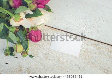 Peony background. Fuchsia, pink and white peonies on white wooden table with an empty card for text. Happy Mothers Day. Mother's Day greetings card. Valentines Day. Copy space. Toned image. - stock photo