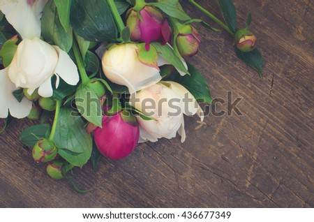 Peony background. Fuchsia, pink and white peonies on wooden table with place for text. Spring flower peony. Happy Mothers Day. Mother's Day greetings card. Mothers Day gift. Copy space. Toned image. - stock photo