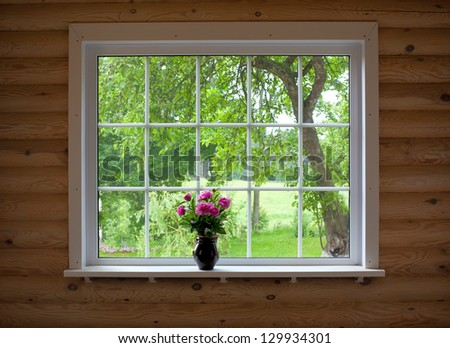 peony flowers on wood log house window-sill - stock photo