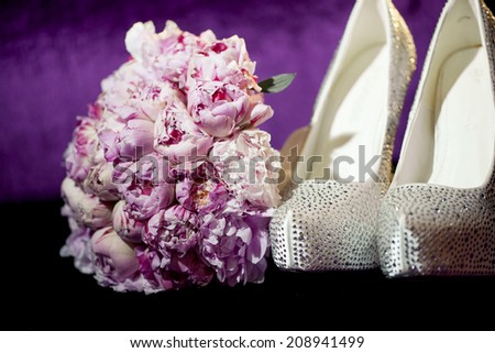 Peony flowers. Wedding bouquet with shoes  on violet background - stock photo
