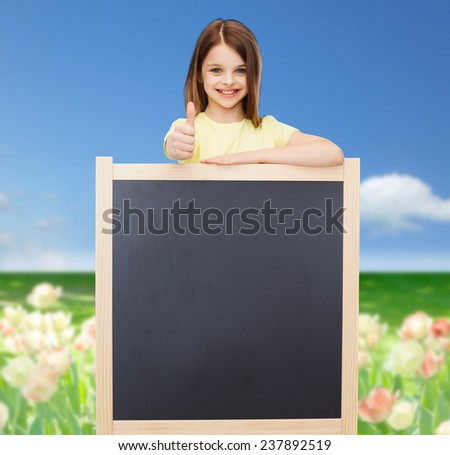 people, advertisement and education concept - happy little girl with blank blackboard showing thumbs up - stock photo