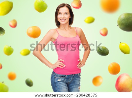 people, advertisement, diet, food and healthy eating concept - smiling woman in blank pink tank top over fruits on green background - stock photo