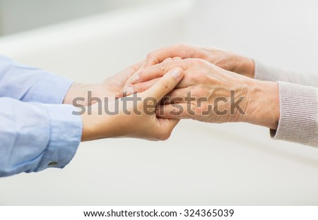 people, age, family, care and support concept - close up of senior and young woman  holding hands - stock photo