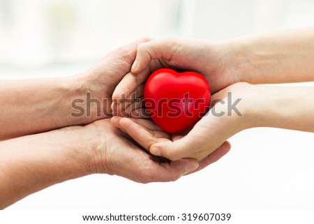 people, age, family, love and health care concept - close up of senior woman and young woman hands holding red heart - stock photo