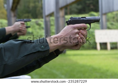 people aiming guns in shooting range - stock photo