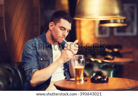 people and bad habits concept - man drinking beer and smoking cigarette at bar or pub - stock photo
