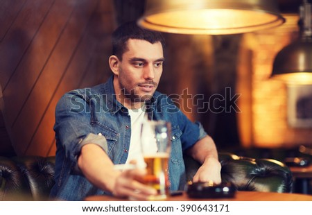 people and bad habits concept - young man drinking beer and smoking cigarette at bar or pub - stock photo