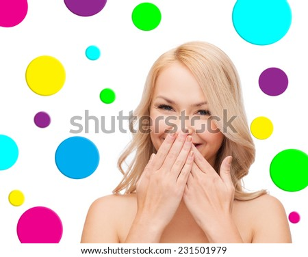 people and beauty concept - beautiful smiling young woman winking one eye over colorful polka dot pattern background - stock photo