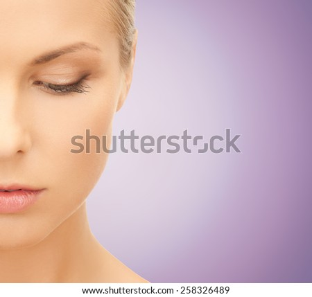 people and beauty concept - close up of beautiful young woman half face looking down over violet background - stock photo