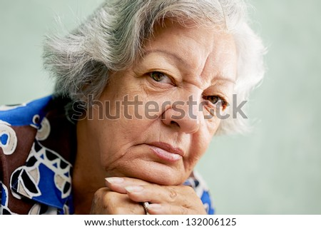 people and emotions, portrait of depressed senior hispanic woman with white hair looking at camera, leaning with hands on chin - stock photo