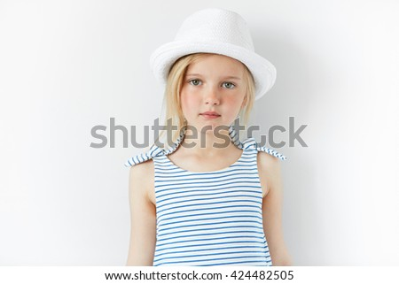 People and lifestyle concept. Close up of happy little female model posing against white concrete wall, wearing white hat and striped dress. Adorable blonde preschool girl looking at the camera  - stock photo