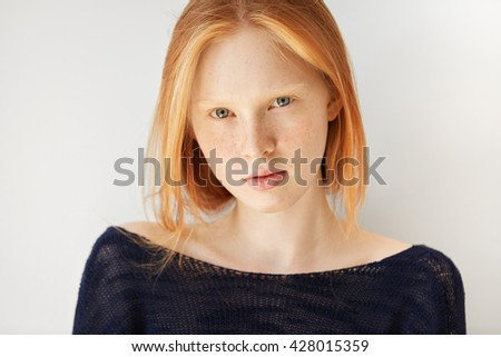 People and lifestyle concept. Headshot of redhead student girl wearing stylish black top, having rest at home after classes at university. Cute hipster woman with healthy skin looking at the camera - stock photo