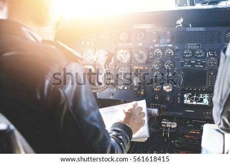 People and occupation concept. Adult captain of jet airliner wearing black leather jacket and headset sitting in front of onboard instruments, filling in safety report before departure. Blurred shot