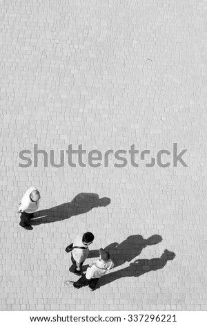 People and shadows. Silhouettes of people throwing out shadows on city street. Top view of paving. Black and white photo