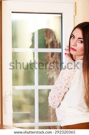 People and solitude concept. Beautiful alone serious woman long hair looking dreaming through window indoor - stock photo