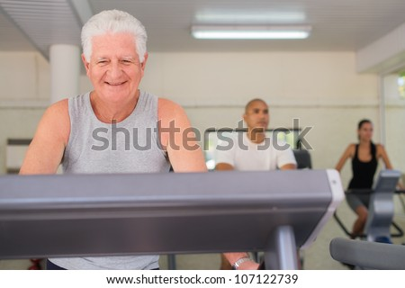 People and sports, elderly man working out on treadmill in fitness gym among young people - stock photo
