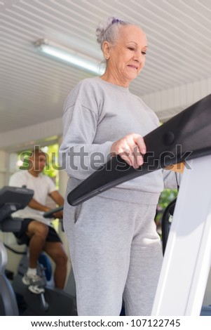 People and sports, elderly woman working out on treadmill in fitness gym - stock photo