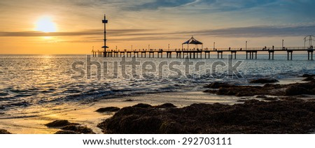 People are fishing on the Brighton Beach Jetty at sunset - stock photo