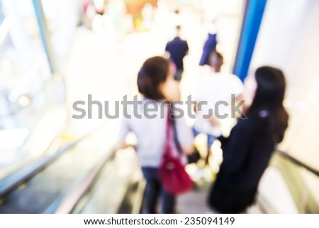 People are going down the escalator. Blur background. - stock photo
