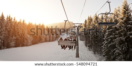 People are lifting on ski-lift in the mountains