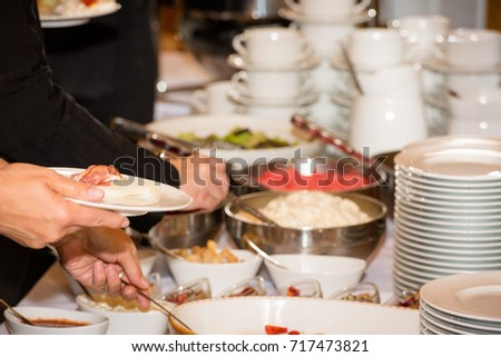 People are picking food from a buffet in a restaurant during a festive event with assorted salads