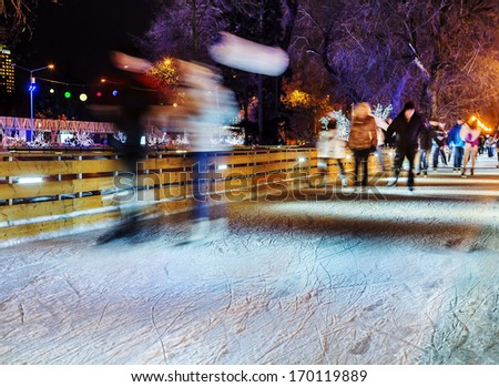 People are skating in the park on a winter skating rink - stock photo