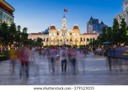 People are walking and taking pictures in front of the City Hall building, Ho Chi Minh City, Vietnam. - stock photo