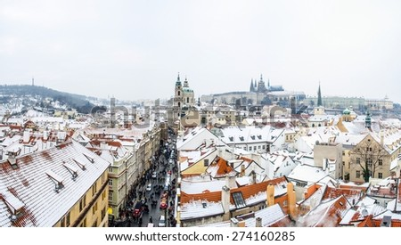 people are walking from the charles bridge towards prague castle in prague, whose rooftops are covered by snow. - stock photo