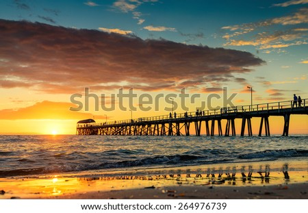 People are walking on the Henley Beach Jetty at sunset - stock photo