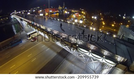 People are walking on the Patriarchal bridge in Moscow at night, aerial view