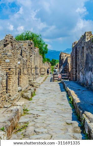 people are walking through ruins of the historical city of pompeii. - stock photo