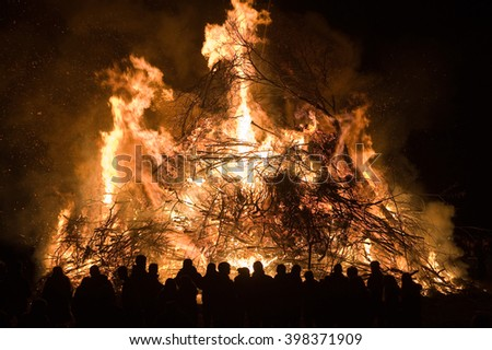 People are watching a huge bonfire, a tradition with easter in North-West Europe.