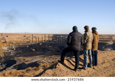 People are watching coal mining from vista point - stock photo