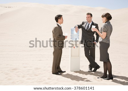 People around water cooler in the desert - stock photo