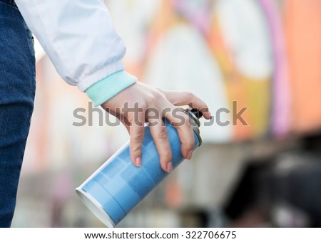 people, art, creativity and youth culture concept - close up of hand drawing graffiti with spray paint on street wall - stock photo