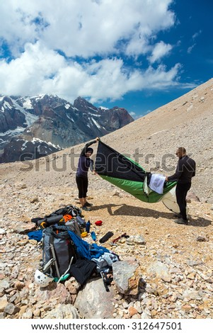 People Assembling Bivouac.  Group of Alpine Climbers Working on setting up Camping Tents with Many Gear Dropped Around and Rocky Mountain Moraine on Background - stock photo