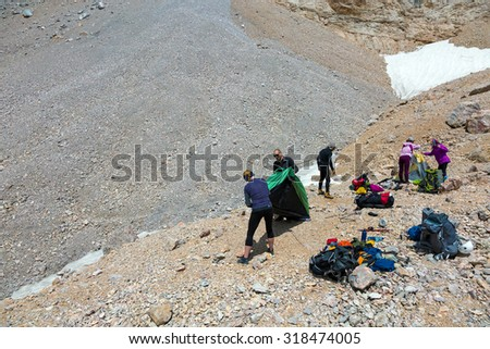 People Assembling Bivouac Group of Alpine Climbers Working on setting up Camping Tents with Many Gear Dropped Around and Rocky Mountain Moraine on Background - stock photo