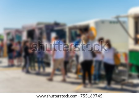 People at a street food market festival on a sunny day. Blurred on purpose.