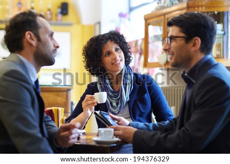 People at bar with team of colleagues meeting in cafeteria, working with  and drinking coffee - stock photo