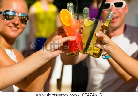 People at beach drinking having a party, friends clinking glasses with cocktails and beer having fun