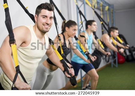 People at gym doing elastic rope exercises - stock photo