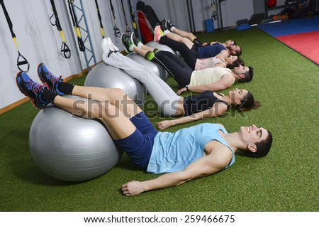 People at gym training abs with balloon. - stock photo
