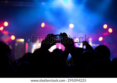 People at rock concert taking photos with cell phone - stock photo