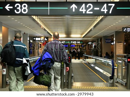 People at the airport going to the gate - stock photo