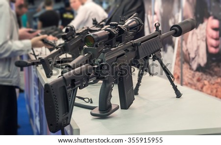 People at the counter with samples of automatic weapons - stock photo