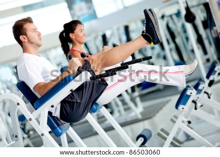 People at the gym exercising their abs on a machine - stock photo