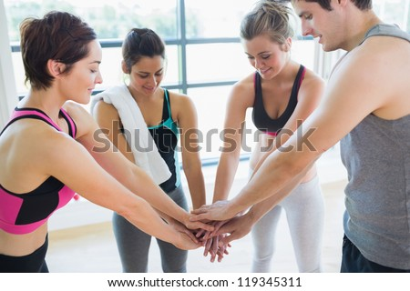 People at the gym putting hands together in fitess studio - stock photo